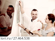 Купить «Couple is doing repair and hanging picture on the wall», фото № 27464538, снято 19 октября 2017 г. (c) Яков Филимонов / Фотобанк Лори