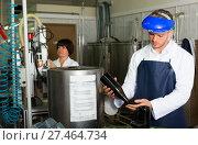 Купить «worker using machine at wine factory», фото № 27464734, снято 10 ноября 2016 г. (c) Яков Филимонов / Фотобанк Лори