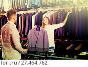 Купить «Female seller demonstrating numerous suits», фото № 27464762, снято 22 июля 2019 г. (c) Яков Филимонов / Фотобанк Лори