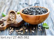 Купить «Sunflower seeds in a wooden bowl closeup», фото № 27465082, снято 3 апреля 2017 г. (c) Марина Сапрунова / Фотобанк Лори