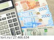 Купить «Купюры номиналом тысяча, две тысячи и пять тысяч рублей и калькулятор на столе», эксклюзивное фото № 27466634, снято 25 января 2018 г. (c) Яна Королёва / Фотобанк Лори