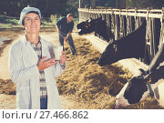 Купить «Female farmer is standing with glass of cow milk at the farm.», фото № 27466862, снято 24 октября 2017 г. (c) Яков Филимонов / Фотобанк Лори