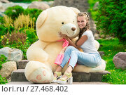 beautiful young girl hugging her beloved big teddy bear in the park on the stairs. Стоковое фото, фотограф Константин Лабунский / Фотобанк Лори