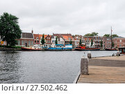 Купить «Picturesque cityscape with beautiful traditional houses and vessels in canal of Haarlem», фото № 27502462, снято 25 марта 2019 г. (c) age Fotostock / Фотобанк Лори