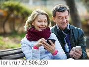 Купить «Pleasant elderly couple with mobile phones», фото № 27506230, снято 19 февраля 2019 г. (c) Яков Филимонов / Фотобанк Лори