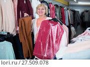 Купить «woman holding jumper, pants and jacket», фото № 27509078, снято 20 декабря 2017 г. (c) Яков Филимонов / Фотобанк Лори