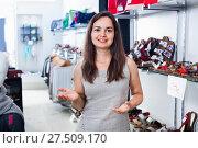 Купить «Brunette offers footwear in fashion shoes center», фото № 27509170, снято 26 сентября 2016 г. (c) Яков Филимонов / Фотобанк Лори