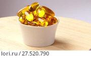 Купить «cup with yellow pills on wooden board», видеоролик № 27520790, снято 26 ноября 2017 г. (c) BestPhotoStudio / Фотобанк Лори