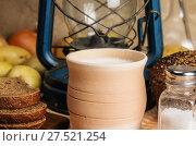 Купить «Молоко в керамической посуде, ржаной хлеб, солонка с солью, овощи и керосиновый фонарь на деревянном столе. Натюрморт в деревенском стиле», фото № 27521254, снято 25 января 2018 г. (c) Вадим Орлов / Фотобанк Лори