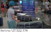 Купить «Boy looking for his suitcase on baggage conveyor belt at the airport», видеоролик № 27522174, снято 19 июня 2018 г. (c) Данил Руденко / Фотобанк Лори