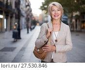 Купить «Cheerful mature female is walking in classic jacket», фото № 27530846, снято 3 сентября 2017 г. (c) Яков Филимонов / Фотобанк Лори