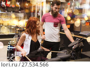 Купить «couple of musicians with drum kit at music store», фото № 27534566, снято 11 декабря 2014 г. (c) Syda Productions / Фотобанк Лори