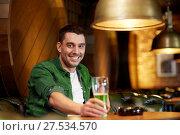Купить «man drinking green beer at bar or pub», фото № 27534570, снято 22 апреля 2015 г. (c) Syda Productions / Фотобанк Лори