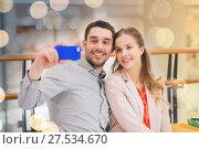 Купить «happy couple with smartphone taking selfie in mall», фото № 27534670, снято 10 ноября 2014 г. (c) Syda Productions / Фотобанк Лори