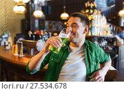 Купить «man drinking green beer at bar or pub», фото № 27534678, снято 22 апреля 2015 г. (c) Syda Productions / Фотобанк Лори