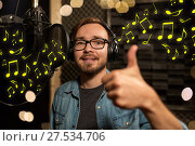 Купить «man with headphones singing at recording studio», фото № 27534706, снято 18 августа 2016 г. (c) Syda Productions / Фотобанк Лори