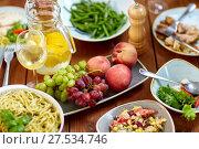 Купить «fruits, salads and pasta on wooden table», фото № 27534746, снято 5 октября 2017 г. (c) Syda Productions / Фотобанк Лори
