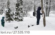 Moscow, Russia - January 31. 2018. Mom and daughter feed pigeons in snow. Редакционное видео, видеограф Володина Ольга / Фотобанк Лори