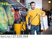 Купить «Adult guy deciding on best garden sprayer», фото № 27535394, снято 2 марта 2017 г. (c) Яков Филимонов / Фотобанк Лори