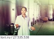 Купить «Female in uniform standing in winery compartment», фото № 27535538, снято 15 сентября 2019 г. (c) Яков Филимонов / Фотобанк Лори