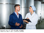 Купить «two workers in coats on winery manufactory», фото № 27535546, снято 22 июля 2018 г. (c) Яков Филимонов / Фотобанк Лори