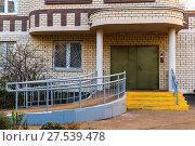 Купить «Entrance to modern high-rise building made of bricks.», фото № 27539478, снято 8 ноября 2017 г. (c) Володина Ольга / Фотобанк Лори