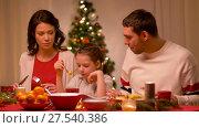 Купить «happy family having christmas dinner at home», видеоролик № 27540386, снято 17 января 2018 г. (c) Syda Productions / Фотобанк Лори