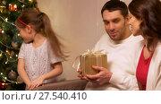 Купить «happy family with christmas present at home», видеоролик № 27540410, снято 17 января 2018 г. (c) Syda Productions / Фотобанк Лори