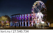 Купить «NIMES, FRANCE - DECEMBER 01, 2017: Spinning ferris wheel near illuminated Arena of Nimes, France», видеоролик № 27540734, снято 1 декабря 2017 г. (c) Яков Филимонов / Фотобанк Лори