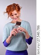 Женщина с рыжими волосами хочет съесть плитку шоколада и улыбается. Стоковое фото, фотограф Максим Мицун / Фотобанк Лори