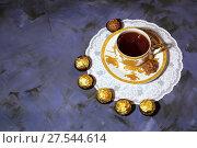 Вечернее чаепитие. Фарфоровая золотистая чашка с чаем и десерт шоколадные конфеты. Evening tea party. Porcelain golden cup with tea and dessert chocolate candy. Стоковое фото, фотограф Светлана Евграфова / Фотобанк Лори