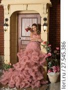 Купить «Девушка в длинном розовом платье стоит у порога дома», фото № 27545386, снято 28 октября 2017 г. (c) Литвяк Игорь / Фотобанк Лори