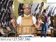 Купить «Male customers try on ammunition with weapon», фото № 27547346, снято 4 июля 2017 г. (c) Яков Филимонов / Фотобанк Лори