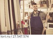 Купить «Smiling male worker deciding on plastic trim corners», фото № 27547574, снято 15 марта 2017 г. (c) Яков Филимонов / Фотобанк Лори
