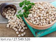 Купить «Wooden bowl with beans chickpea and parsley», фото № 27549526, снято 30 ноября 2016 г. (c) Марина Сапрунова / Фотобанк Лори