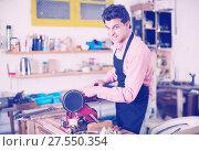 Купить «Carpenter working on manual lathe», фото № 27550354, снято 8 апреля 2017 г. (c) Яков Филимонов / Фотобанк Лори