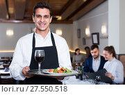 Купить «friendly waiter with serving tray welcoming to restaurant», фото № 27550518, снято 7 ноября 2017 г. (c) Яков Филимонов / Фотобанк Лори
