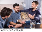 Купить «Three anxious men discussing on sofa», фото № 27550558, снято 10 января 2018 г. (c) Яков Филимонов / Фотобанк Лори