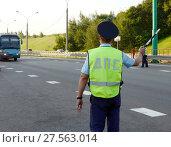 Инспектор дорожно-патрульной службы полиции останавливает для проверки междугородний пассажирский автобус (2017 год). Редакционное фото, фотограф Free Wind / Фотобанк Лори