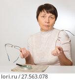 Купить «Женщина недоумевает - очки не подходят. Держит в руках две пары очков», фото № 27563078, снято 5 февраля 2018 г. (c) Юлия Бабкина / Фотобанк Лори