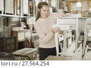Купить «woman buyer standing near nightstand», фото № 27564254, снято 15 ноября 2017 г. (c) Яков Филимонов / Фотобанк Лори