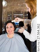 Купить «Hairdresser does to woman haircut with use of scissors and hairbrushes», фото № 27564362, снято 7 марта 2017 г. (c) Яков Филимонов / Фотобанк Лори