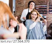 Купить «Woman points to master in hairdress salon right hair length for haircut», фото № 27564370, снято 7 марта 2017 г. (c) Яков Филимонов / Фотобанк Лори