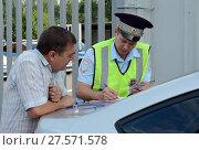Купить «Инспектор дорожно-патрульной службы полиции оформляет протокол о нарушении правил дорожного движения», фото № 27571578, снято 3 августа 2017 г. (c) Free Wind / Фотобанк Лори