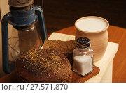 Купить «Ржаной хлеб с солью на разделочной доске, горшок с молоком и керосиновый фонарь. Натюрморт в деревенском стиле», фото № 27571870, снято 25 января 2018 г. (c) Вадим Орлов / Фотобанк Лори