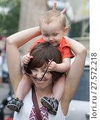 Купить «Молодая женщина играет с ребенком и крепко зажмурила глаза. Малыш сидит у мамы на шее и пытается надеть на нее солнцезащитные очки», фото № 27572218, снято 24 июля 2016 г. (c) Наталья Николаева / Фотобанк Лори