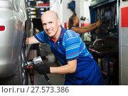 Купить «Mechanic man working with tire», фото № 27573386, снято 19 сентября 2019 г. (c) Яков Филимонов / Фотобанк Лори