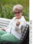Купить «Агрессивная пожилая женщина грозит кулаком, сидя на скамейке в парке», фото № 27581402, снято 8 июня 2017 г. (c) Кекяляйнен Андрей / Фотобанк Лори