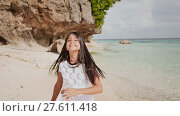 Купить «A charming and happy philippine teenage girl in a white summer dress is running along a tropical beach near the rocks. She is happily spinning. Childhood. Recreation.», видеоролик № 27611418, снято 25 января 2018 г. (c) Mikhail Davidovich / Фотобанк Лори