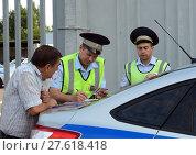 Купить «Инспекторы дорожно-патрульной службы полиции оформляют протокол о нарушении правил дорожного движения», фото № 27618418, снято 3 августа 2017 г. (c) Free Wind / Фотобанк Лори